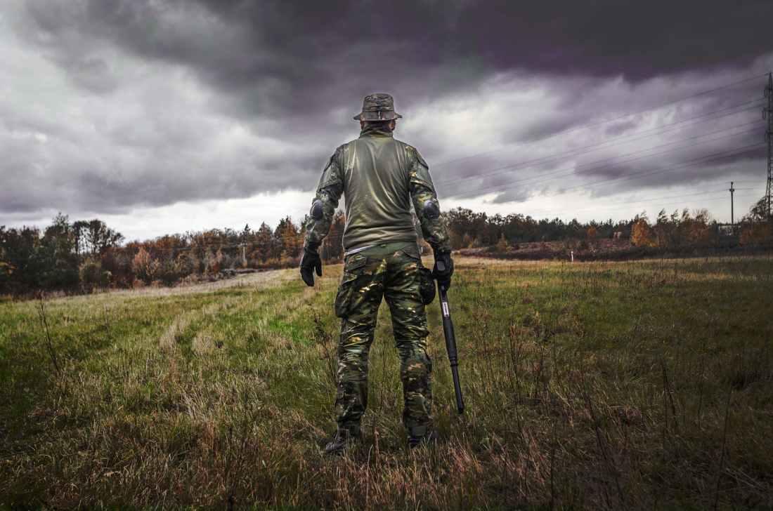 man in camouflage suit holding shotgun